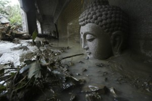 A statue of Buddha's head is seen submerged in flood water and debris from Typhoon Morakot at a temple in Kaohsiung County, southern Taiwan Tuesday, Aug. 11, 2009. Rescue officials have said more than 300 people were ferried from disaster areas on more than 100 emergency flights. (AP Photo)