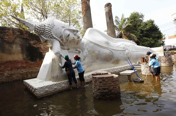 Thai volunteers clean a Buddha statue after flood waters receded at Wat Yai Chaimongkol ancient temple in Ayutthaya province November 10, 2011. REUTERS/Sukree Sukplang (THAILAND - Tags: RELIGION ENVIRONMENT DISASTER)